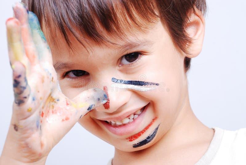 Piccolo bambino sveglio con i colori sul suo fronte fotografia stock libera da diritti