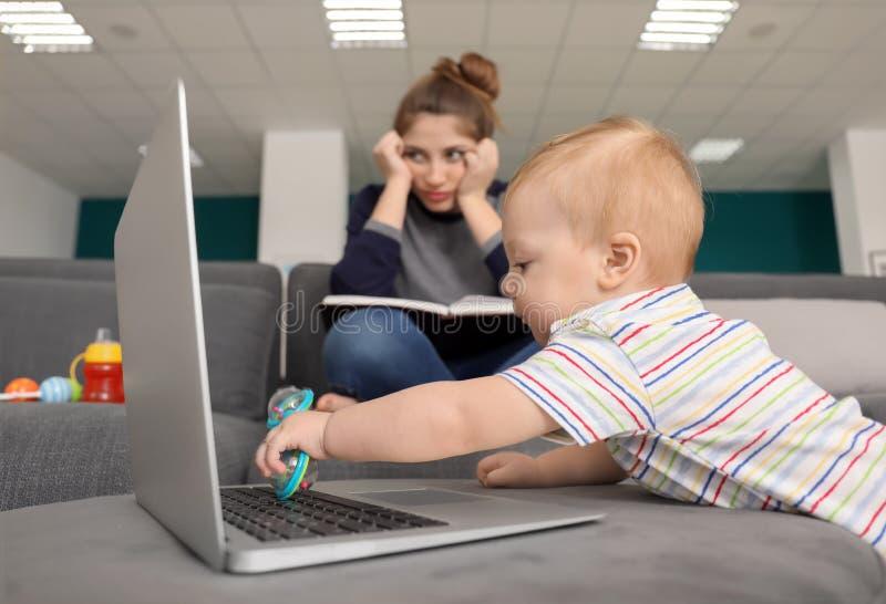 Piccolo bambino sveglio con il computer portatile con la madre stanca a casa fotografie stock libere da diritti