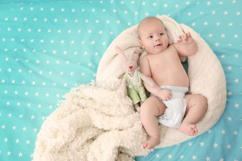 Piccolo bambino sveglio con il giocattolo del coniglietto che si trova sul letto immagine stock libera da diritti