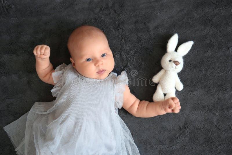 Piccolo bambino sveglio con il giocattolo del coniglietto che si trova sul letto, vista superiore immagini stock