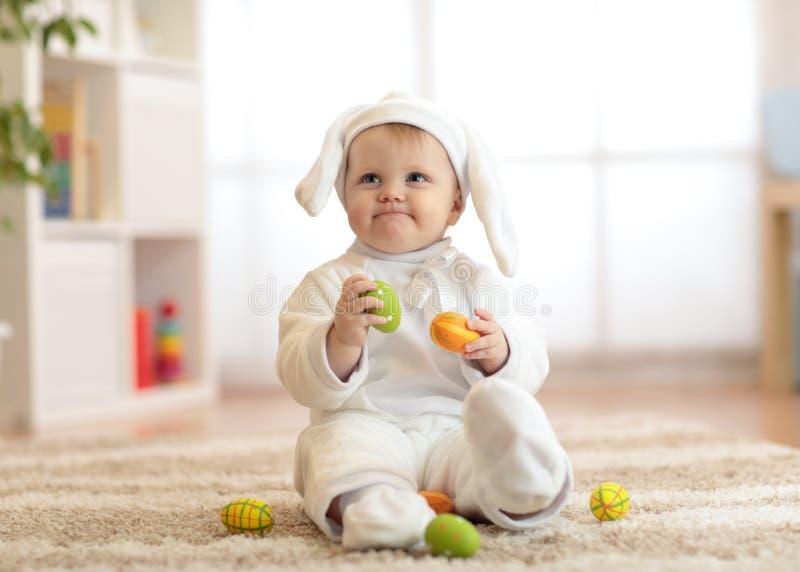 Piccolo bambino sveglio in costume bianco del coniglietto che si siede sulla coperta a casa immagini stock