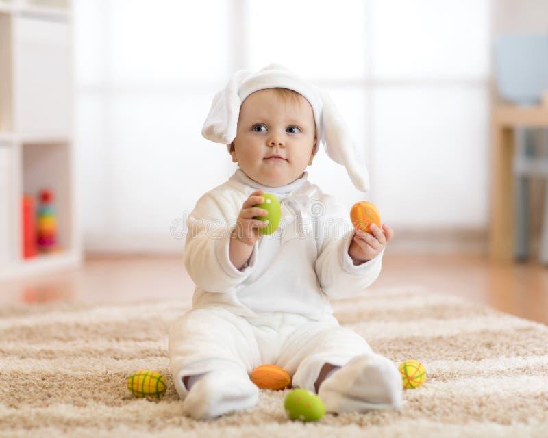 Piccolo bambino sveglio in costume bianco del coniglietto che si siede sulla coperta a casa fotografia stock