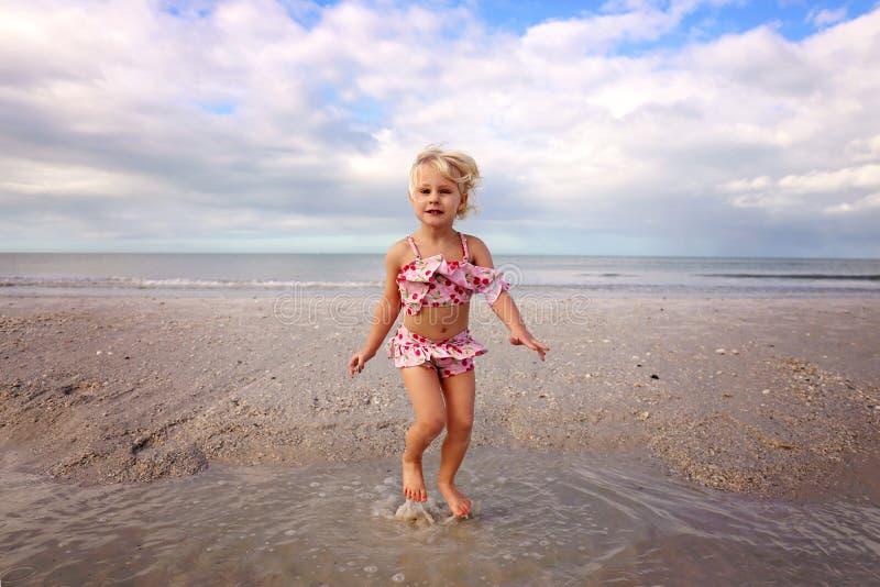 Piccolo bambino sveglio della spiaggia che salta e che gioca nell'acqua dall'oceano immagini stock