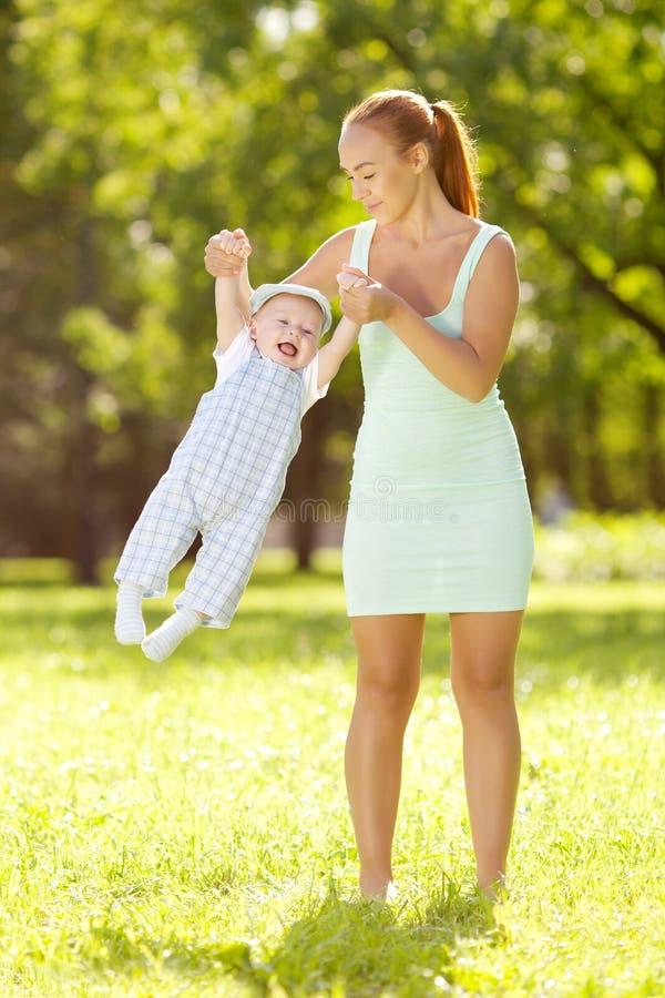 Piccolo bambino sveglio nel parco di estate con la madre sull'erba. Swee fotografia stock