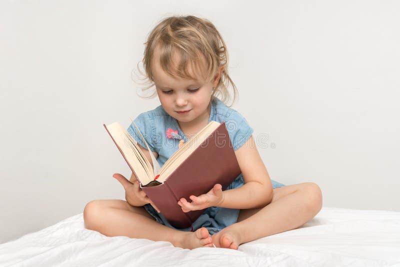 Piccolo bambino sveglio in vestito blu che legge un libro fotografie stock libere da diritti