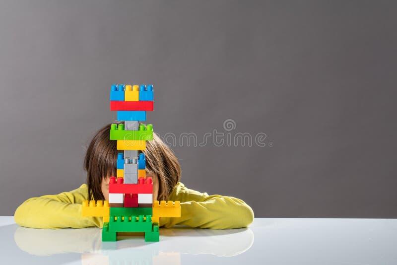 Piccolo bambino timido che si nasconde dietro il giocattolo costruito per psicologia del bambino fotografie stock
