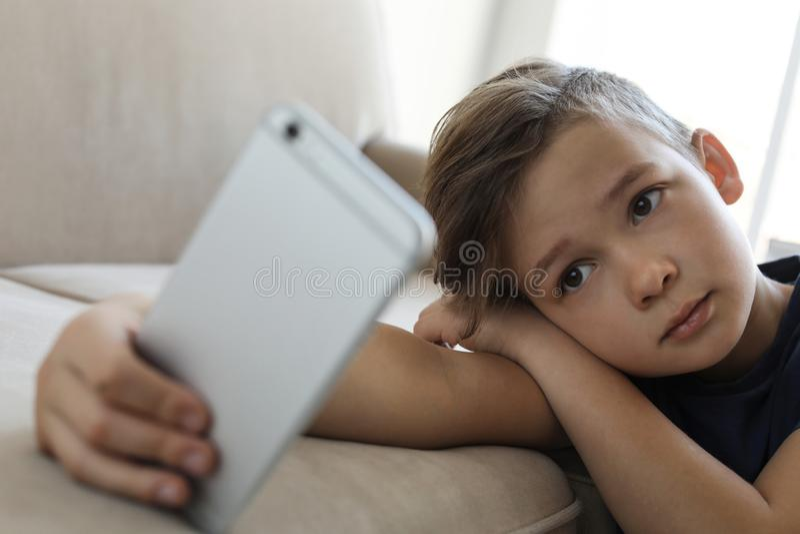 Piccolo bambino triste con lo smartphone che si appoggia sofà Il pericolo di Internet fotografie stock libere da diritti