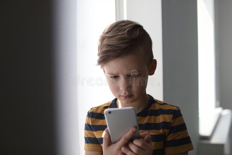 Piccolo bambino triste con lo smartphone Il pericolo di Internet fotografia stock libera da diritti