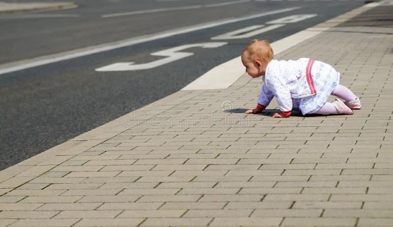 Piccolo bambino in vestiti bianchi che strisciano lungo la strada immagini stock libere da diritti