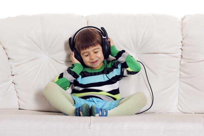Piccolo bel ragazzo sul sofà che ascolta la musica immagine stock libera da diritti
