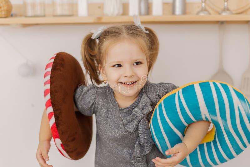 Piccolo bella ragazza che gioca nella cucina con i giocattoli variopinti fotografia stock