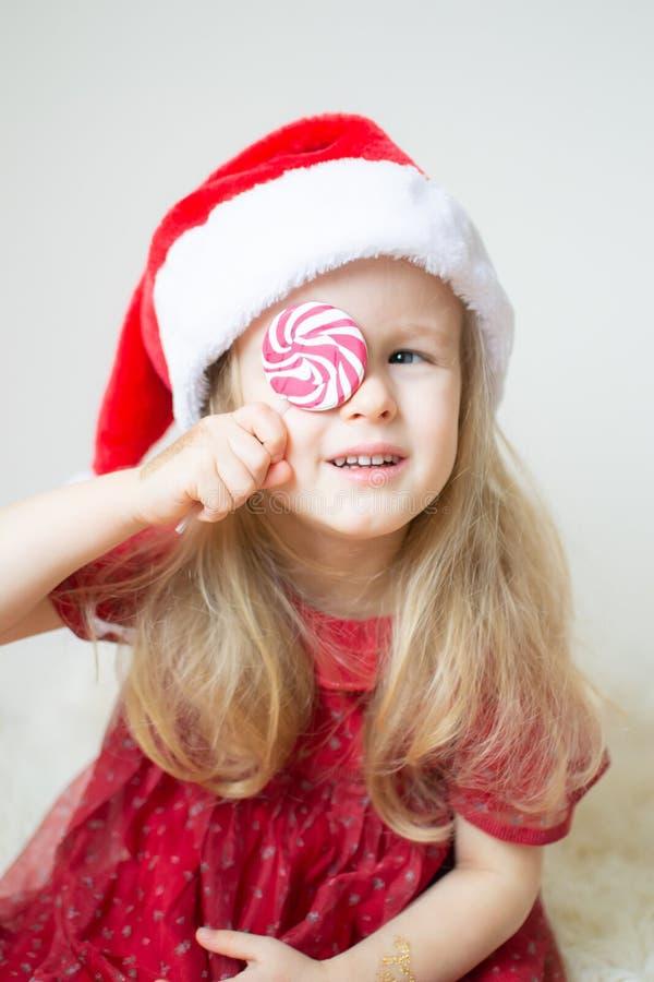Piccolo bella ragazza durante il Natale ed il nuovo anno aspettanti di Santa Hat Red Party Dress immagine stock