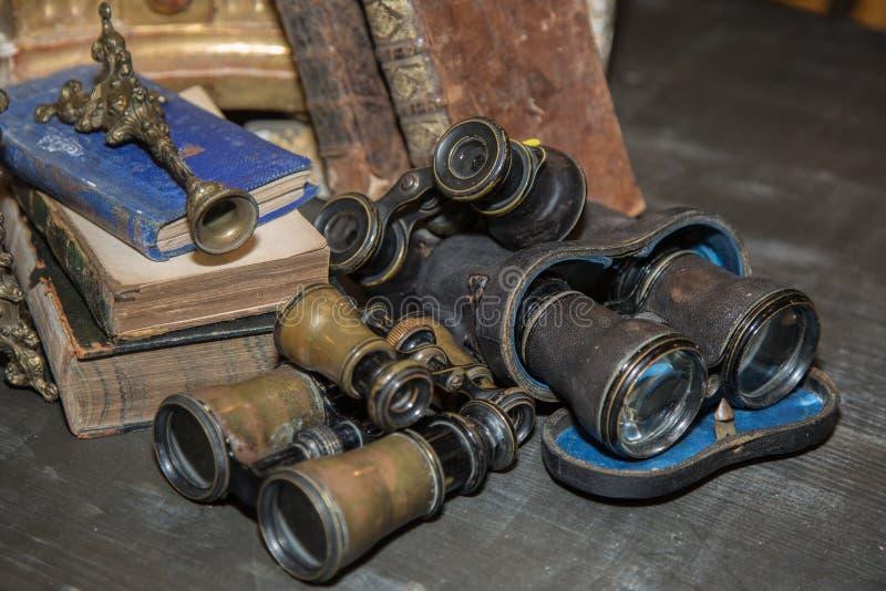 Piccolo binocolo antico accanto ai libri logori fotografia stock