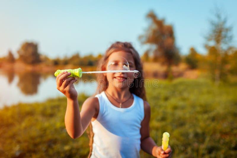 Piccolo bolle di salto della ragazza sveglia nel parco di estate dal fiume Primo piano della bolla di sapone Divertiresi del bamb immagini stock libere da diritti