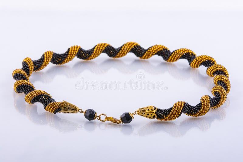 Piccolo braccialetto in rilievo fatto a mano fatto delle perle dell'oro e nere immagine stock libera da diritti