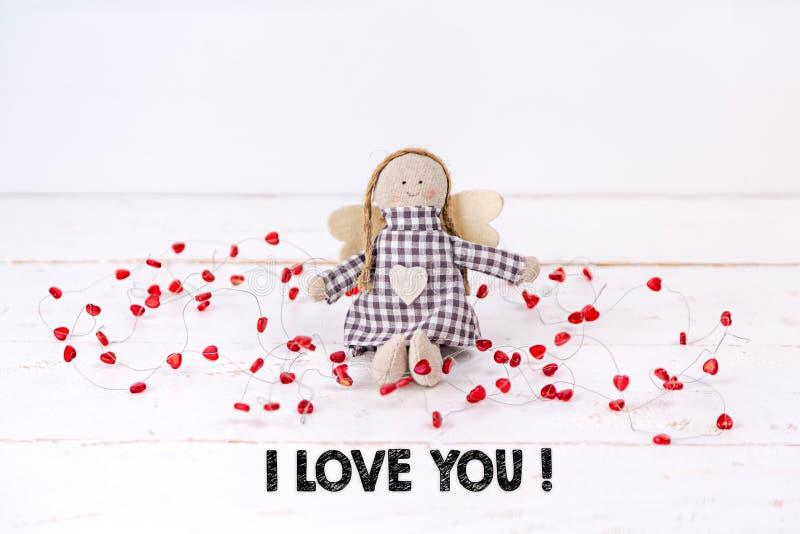 """Piccolo burattino con i cuori rossi che si siedono su un fondo bianco di legno con il testo """"ti amo """" fotografia stock"""