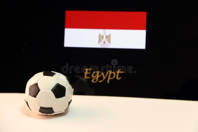 Piccolo calcio sul pavimento bianco e sulla bandiera egiziana di nazione con il testo del fondo dell'Egitto fotografie stock libere da diritti