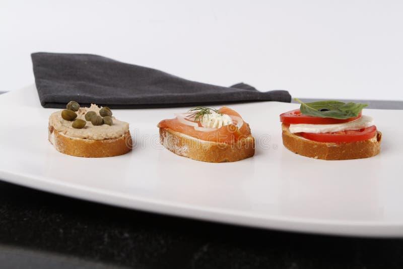 Piccolo canape con il tonno e cappero, pomodoro e mozarella, salmone e cipolle immagine stock libera da diritti