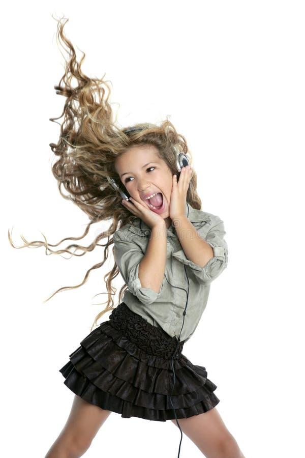 Piccolo canto biondo ballante di musica delle cuffie della ragazza fotografia stock libera da diritti