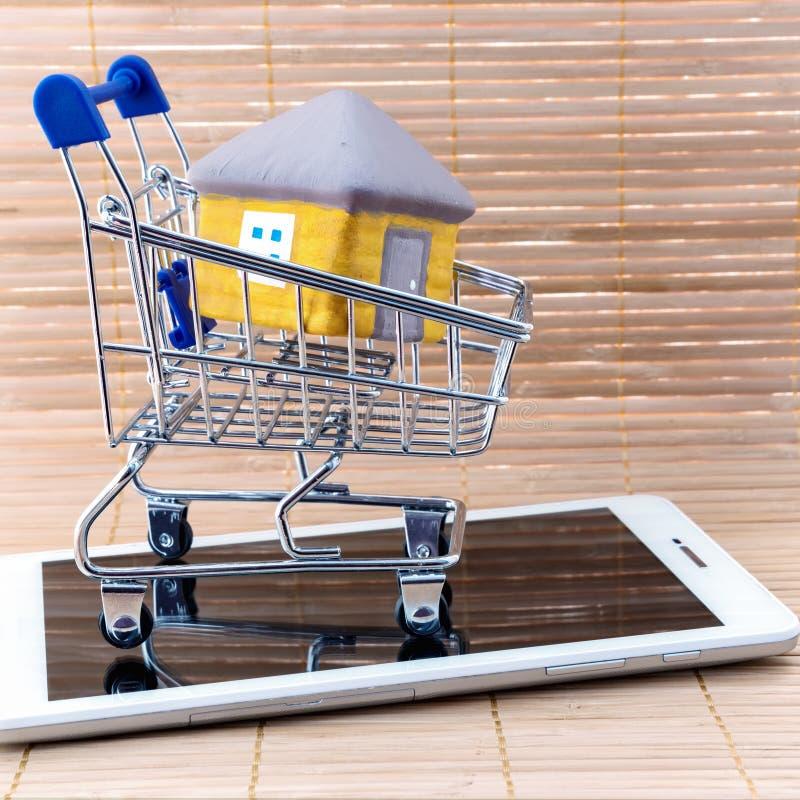 Piccolo carretto del cestino della spesa con la casa sul computer della compressa su fondo del recinto di legno fotografia stock