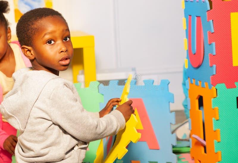 Piccolo casa nera di configurazione del ragazzo delle lettere in scuola materna fotografia stock libera da diritti