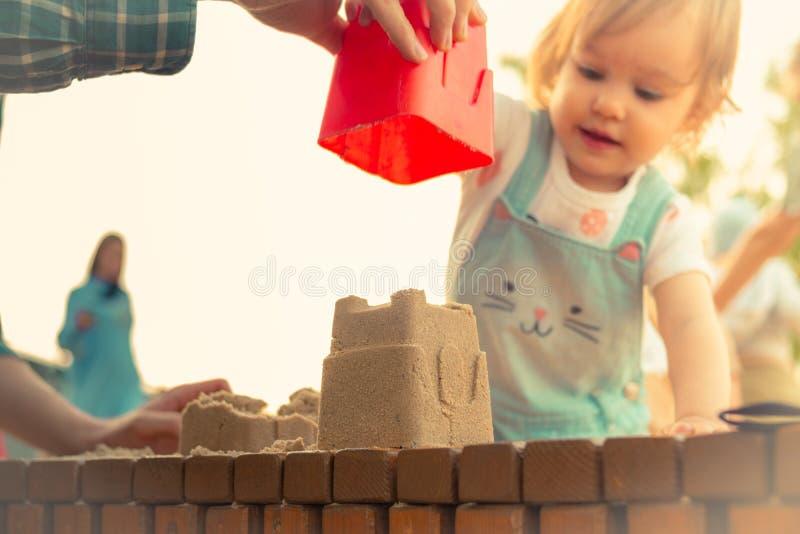 Piccolo castello sorridente della sabbia della costruzione della ragazza in sabbiera di estate fotografie stock libere da diritti