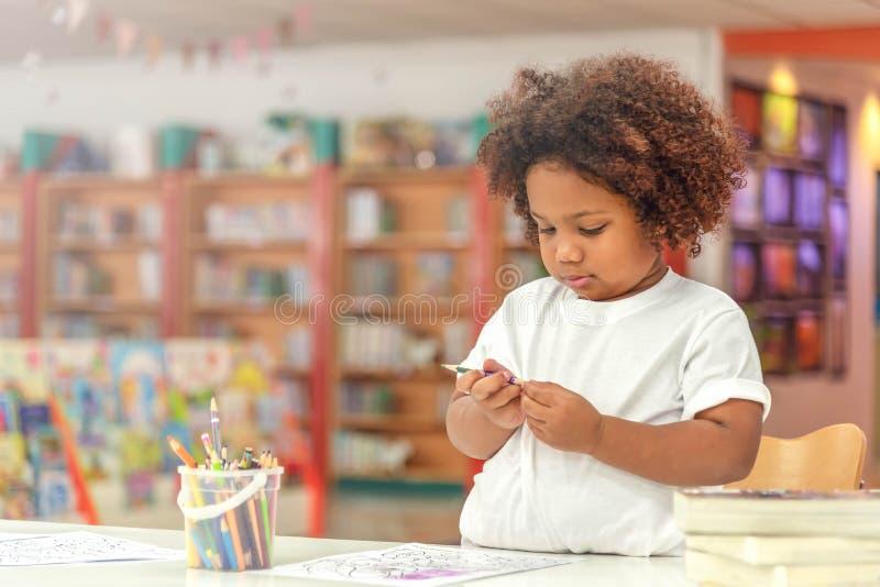 Piccolo concentrato della ragazza del bambino sul disegno Ragazza africana della miscela imparare e giocare nella classe della sc fotografie stock libere da diritti