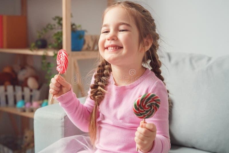 Piccolo concetto sveglio di celebrazione della ragazza a casa che si siede mangiando lecca-lecca fotografia stock libera da diritti