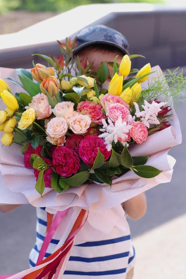 Piccolo condizione sorridente del ragazzo con un mazzo del fiore Bei fiori per la madre fotografie stock
