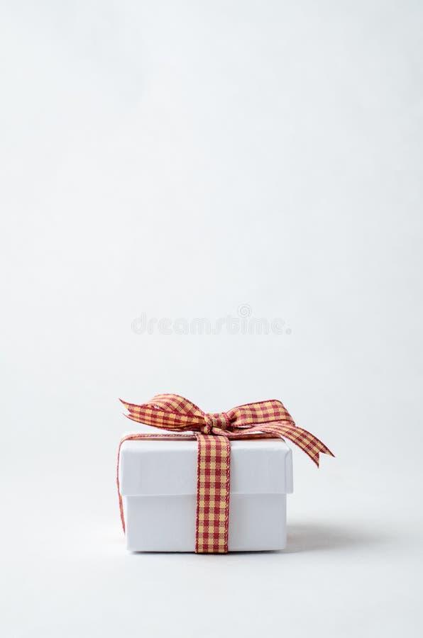 Piccolo contenitore di regalo bianco con il nastro controllato percalle fotografia stock