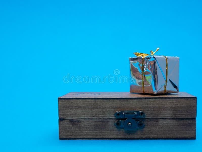 Piccolo contenitore di regalo brillante sul petto di legno immagini stock