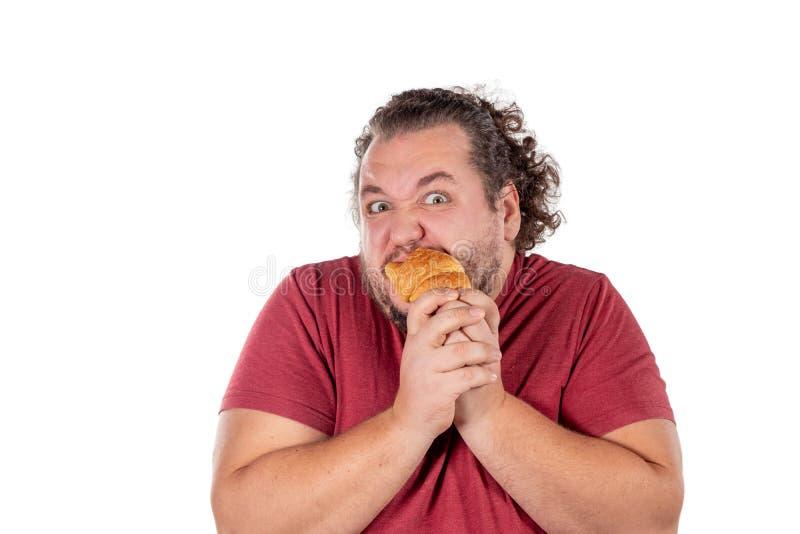 Piccolo croissant mangiatore di uomini grasso divertente su fondo bianco Buongiorno e prima colazione fotografia stock libera da diritti