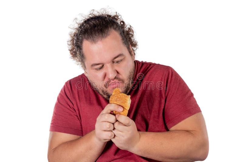 Piccolo croissant mangiatore di uomini grasso divertente su fondo bianco Buongiorno e prima colazione fotografie stock libere da diritti