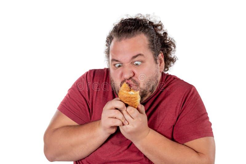 Piccolo croissant mangiatore di uomini grasso divertente su fondo bianco Buongiorno e prima colazione immagini stock libere da diritti