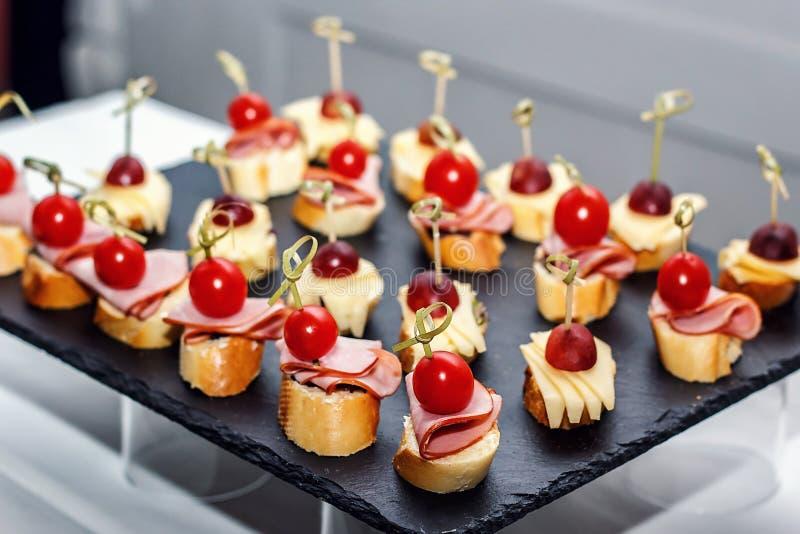 Piccolo crostini con le baguette arrostite, i pomodori ciliegia, le fette del prosciutto, il formaggio e l'uva fresca su fondo ne fotografia stock libera da diritti