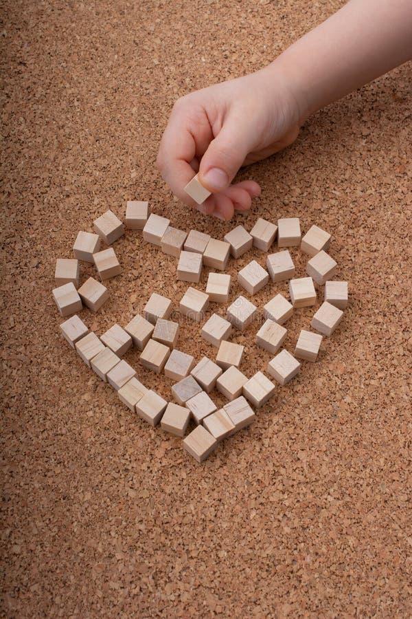 Piccolo cubi di legno forma il simbolo di forma del cuore o del giorno di biglietti di S. Valentino immagini stock