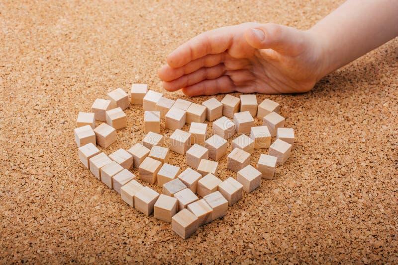 Piccolo cubi di legno forma il simbolo di forma del cuore o del giorno di biglietti di S. Valentino fotografia stock