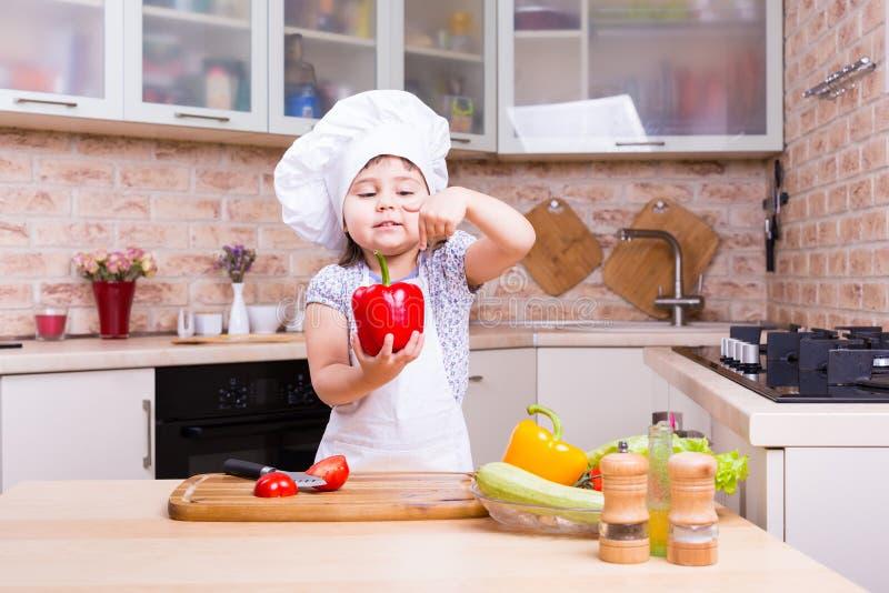 Piccolo cuoco unico sulla cucina che prepara le verdure immagini stock libere da diritti