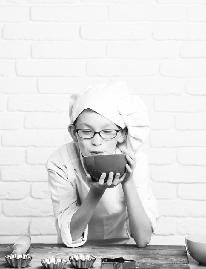 Piccolo cuoco unico sveglio del cuoco del giovane ragazzo in uniforme e cappello di bianco sul fronte divertente con i vetri che  immagine stock