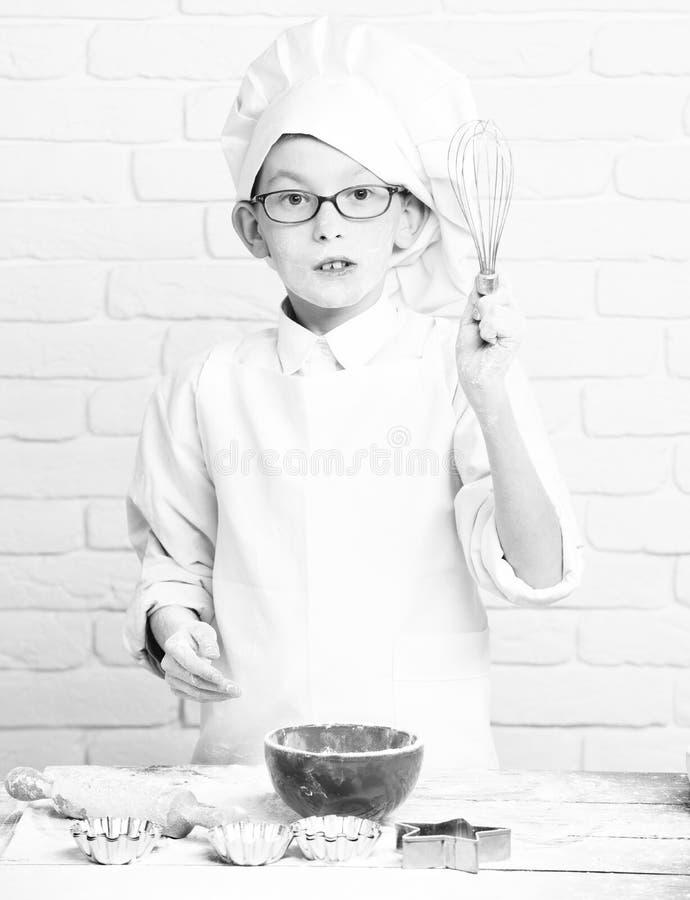 Piccolo cuoco unico sveglio del cuoco del giovane ragazzo in uniforme e cappello di bianco sul fronte felice con i vetri che stan immagini stock
