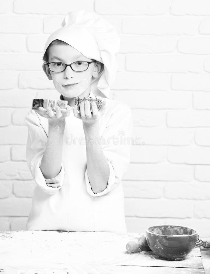 Piccolo cuoco unico sveglio del cuoco del giovane ragazzo in uniforme e cappello di bianco sulla farina macchiata del fronte con  immagine stock libera da diritti