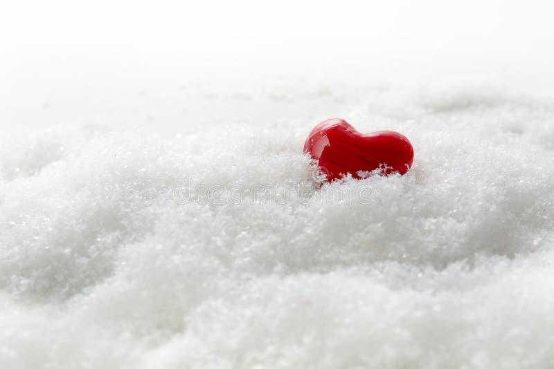 Piccolo cuore rosso nella neve bianca, spazio generoso della copia, concetto fotografie stock