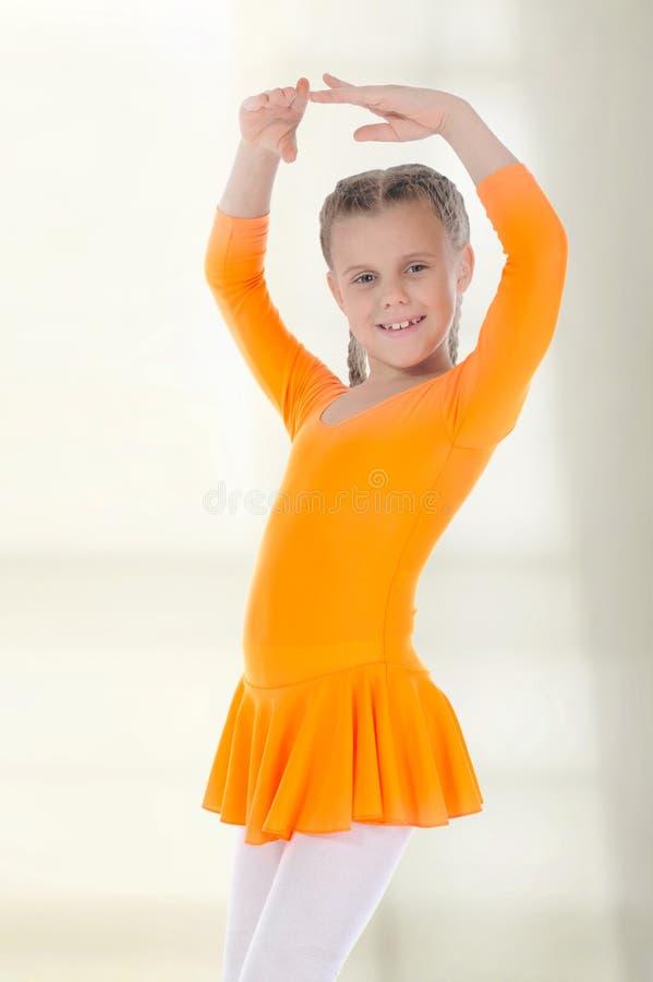 Piccolo dancing della ballerina in un vestito arancione. fotografia stock libera da diritti
