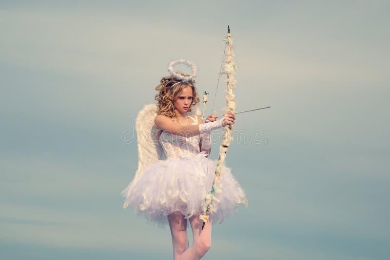 Piccolo dea con le ali bianche da solo sul fondo del cielo blu Bambino delle ali di angelo Bambino con il carattere angelico poco immagine stock