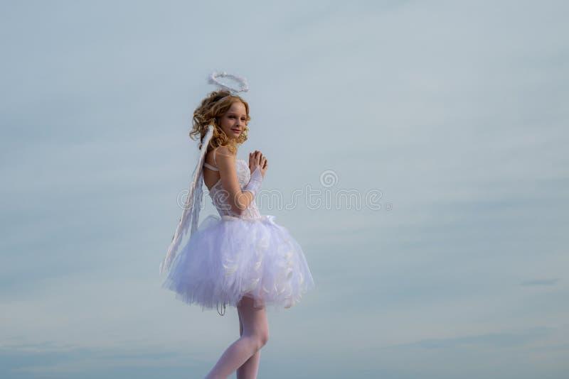 Piccolo dea con le ali bianche da solo sul fondo del cielo blu L'angelo del cherubino prega cielo Angelo teenager cherub Angelo d immagini stock