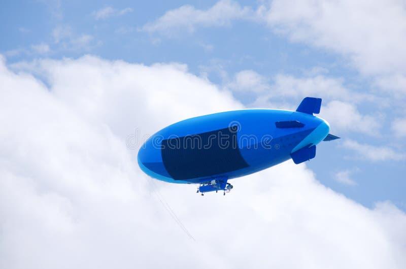 Piccolo dirigibile di volo con zona in bianco del segno di pubblicità immagine stock libera da diritti