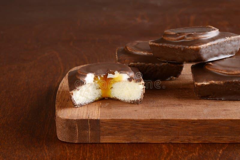 Piccolo dolce coperto di cioccolato tagliato della vaniglia riempito di salsa del caramello e della crema fotografia stock libera da diritti