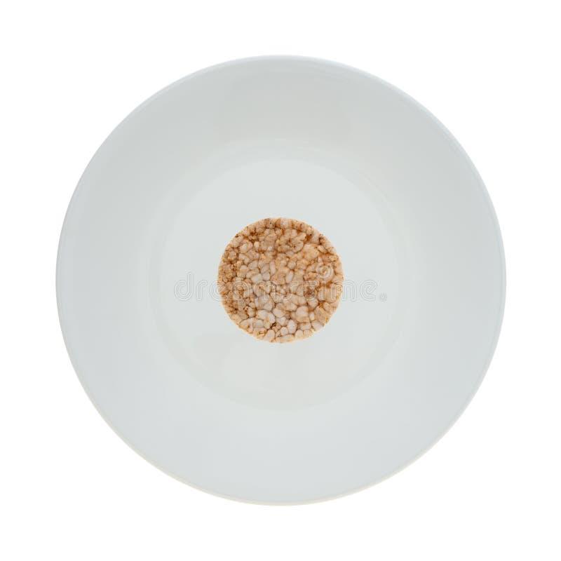 Piccolo dolce di riso del multigrain su un piatto bianco fotografia stock libera da diritti