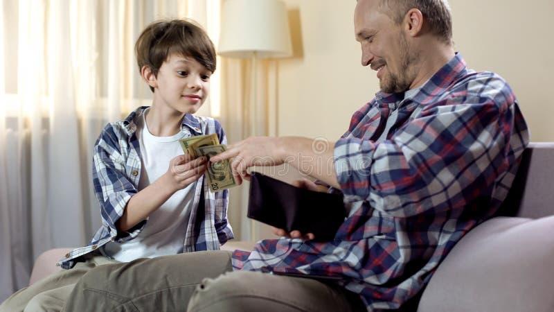 Piccolo figlio che chiede al padre di dare più denaro per piccole spese, bisogni finanziari, paternità fotografia stock