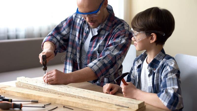 A piccolo figlio del papà insegnando a come usare sicuro martello, svago della famiglia, hobby e divertimento fotografie stock libere da diritti